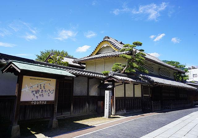 菱格子の出窓や、流れるような屋根が特徴的な建築の「旧松阪家住宅」