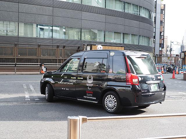 올림픽 로고가 인쇄된 블랙 외관의 택시 JPN TAXI